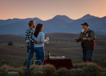 Traditional owner man talking to a man and woman
